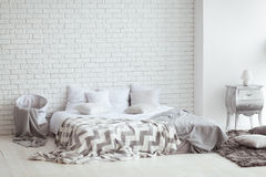 Bedroom interior with a brick wall with a bed and bedside tables.  Royalty Free Stock Image