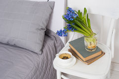 Bedroom interior closeup. Clean white bedroom interior closeup, cup of tea and hyacinth flowers on a chair. Home interior decor royalty free stock photos