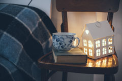 Bedroom interior closeup. Cozy vintage bedroom interior closeup, cup of tea and a night light on a chair. Home interior decor with blue plaid and warm light royalty free stock photography