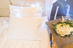 Bedroom interior closeup. White pillows, night table with flowers, hygge lifestyle stock image