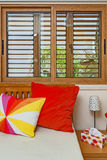 Bedroom interior. Colourful pillows. Wooden window Royalty Free Stock Images