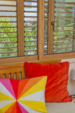 Bedroom interior. Colourful pillows. Wooden window Stock Photos