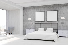 Bedroom interior with concrete walls, a large bed with two square posters. Royalty Free Stock Photography
