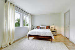 Bedroom interior in light tones with wooden bed and hardwood floor. Royalty Free Stock Image