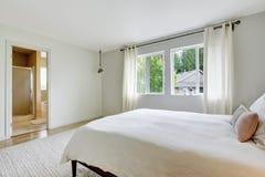 Bedroom interior in light tones with wooden bed and hardwood floor. Stock Images