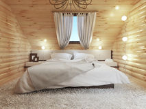 Bedroom interior in a log on the attic floor with a roof window. Royalty Free Stock Photography