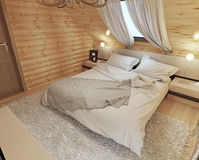 Bedroom interior in a log on the attic floor with a roof window. Royalty Free Stock Image