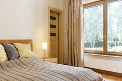 Bedroom interior with marital bed. Quiet bedroom interior with marital bed and window with the view of the garden Stock Image