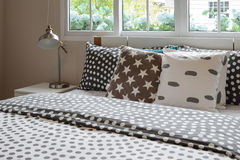 Bedroom interior with polka dot pillows on bed and decora. Bedroom interior design with polka dot pillows on bed and decorative bedside table lamp Stock Image