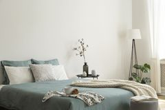Bedroom interior with sage green and white sheets and cushions and a blanket. Black metal table with vases beside the bed. A lamp. Standing in the corner. Real stock image