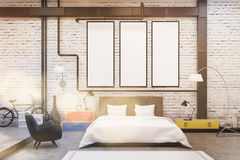 Bedroom interior with white walls and three narrow vertical posters on them. Stock Images