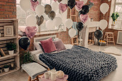 Bedroom with large bed and balloons stock images