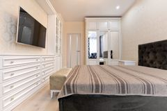 Bedroom in light colors with wooden white furniture royalty free stock images