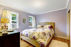 Bedroom in light lavender color. With ivory floral bedding stock photo