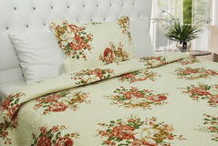 Bedroom linen. Elegant floral bedroom linen on king size bed Stock Image
