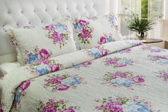 Bedroom linen. Elegant floral bedroom linen on king size bed Royalty Free Stock Photography