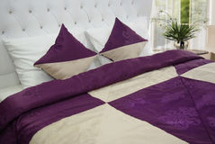 Bedroom linen. Elegant purple bedroom linen on king size bed Royalty Free Stock Images