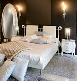 Bedroom modern silver oval mirror white bed. Black wall Stock Photography