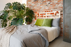 Bedroom with monstera. Modern bedroom with brick wall, king-size bed and monstera Royalty Free Stock Photos
