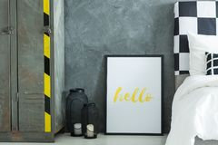 Bedroom with poster on floor. Lanterns and poster with yellow word hello on floor in bedroom with industrial metal shelf and black an white pillows on bed stock photos