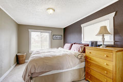 Bedroom with queen size comfortable bed. Contrast color wall in dark brown and light grey colors Stock Photos
