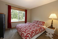 Bedroom with red bed and brown walls Royalty Free Stock Photography