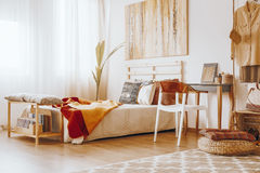 Bedroom in sandy colors. Wooden bed with blanket and pillows standing in cozy bedroom in sandy colors royalty free stock photography