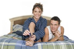Bedroom scene. Woman painting her toe nails while having a relaxed talk with her husband on the bed royalty free stock images