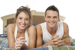 Bedroom scene. Happy young couple sitting on bed stock photography