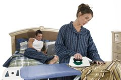 Bedroom scene - Ironing. Woman ironing her husband's shirt while he is working on his laptop stock image