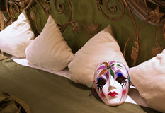 Bedroom secrets. Secrets in bed concept: Mask on a pillow in a luxury bedroom Stock Image