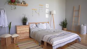 Bedroom set with cozy accessories in the Scandinavian style. A bed with a large number of pillows, soft carpets and stock footage