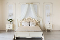 Bedroom in soft light colors. Big comfortable double bed in elegant classic interior Royalty Free Stock Photography