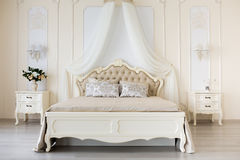 Bedroom in soft light colors. Big comfortable double bed in elegant classic interior Stock Photography