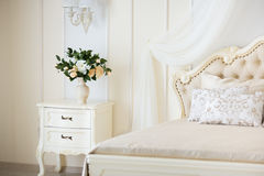 Bedroom in soft light colors. Big comfortable double bed in elegant classic interior.  Royalty Free Stock Photos
