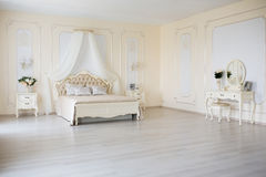 Bedroom in soft light colors. Big comfortable double bed in elegant classic interior.  Royalty Free Stock Image
