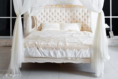 Bedroom in soft light colors. Big comfortable four poster double bed in elegant classic bedroom. Luxury white with gold interior d Royalty Free Stock Image