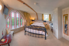 Bedroom with stained-glass window (The Belfry) Stock Photography
