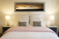 Bedroom and framed picture of a sunset royalty free stock photos