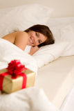Bedroom surprise present - young happy woman Stock Photography