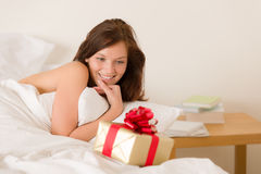 Bedroom surprise present - young happy woman Stock Photo