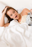 Bedroom surprise - woman with alarm clock wake up Royalty Free Stock Photo