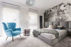Bedroom with vintage blue armchair. Monochromatic gray bedroom with grunge wall, wooden bedside table, white walls and blue vintage style armchair stock photo