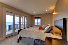 Bedroom with water view and beuge walls. Stock Photos