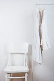Bedroom white interior, clothes on the hanger Stock Photos