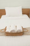 Bedroom White. White towel in wicker basket placed on the bed Royalty Free Stock Photography