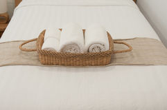 Bedroom White. White towel in wicker basket placed on the bed Stock Photography