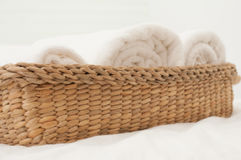 Bedroom White. White towel in wicker basket placed on the bed Stock Images