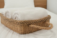 Bedroom White. White towel in wicker basket placed on the bed Royalty Free Stock Photo