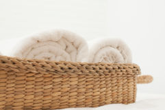 Bedroom White. White towel in wicker basket placed on the bed Royalty Free Stock Image